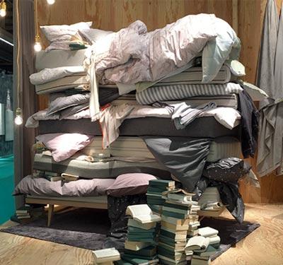 gestapelte Matratzen, Decken und Kissen